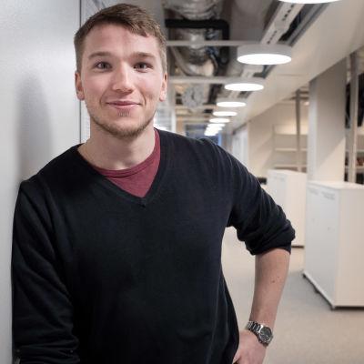 Aron Larsson lutar sig mot en vit vägg i ett kontorslandskap.