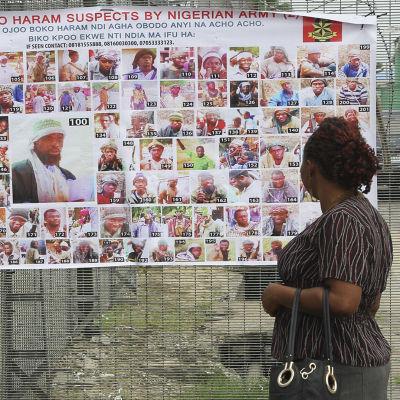 En nigeriansk kvinna ser på en plansch med bilder på misstänkta och efterlysta medlemmar av Boko Haram