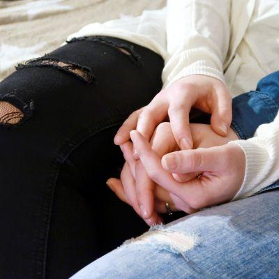 Kädet toisiinsa kietoutuneina pariskunnan sylissä sohvalla