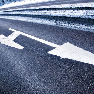 Valkoisella maalilla maalatut ryhmittymisnuolimerkit asfaltin päällä.