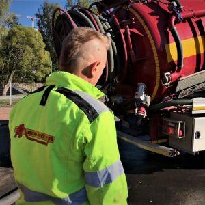 Mies seuraa jäteauton tyhjentämistä jätevesipuhdistamolla.