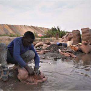 DieuDonné sitter på huk och tvättar kobolt vid en flod.