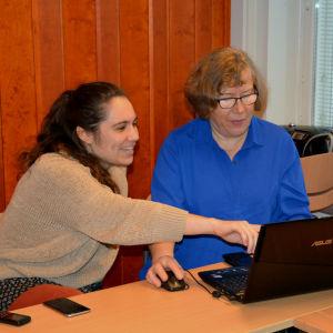 Luisa sitter bredvid Eva och pekar på dataskärmen som Eva har framför sig.