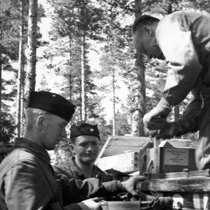 Autosta jaetaan tarvikkeita sotilaille Kannaksella.