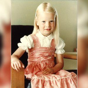 Outi Pyy yllään pinkki mekko, jonka alla on valkoinen, puhvihihoilla varustettu paita. Hän istuu sohvalla ja katse on kameraan.