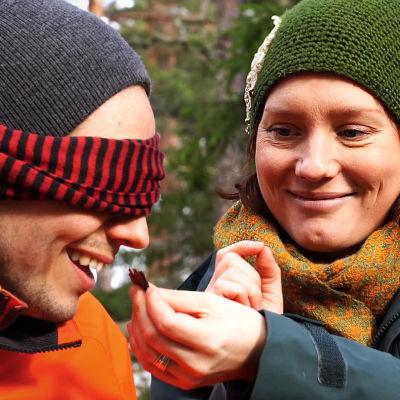 En bild på en man som luktar på bark som en kvinna håller i handen. mannen har ögonbindel.