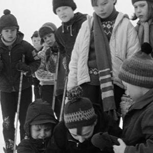 Koulupojat auttavat loukkaantunutta ystäväänsä hiihtomäessä (1966).
