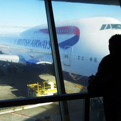 Matkustaja katselee lentokoneita lentoaseman ikkunasta.