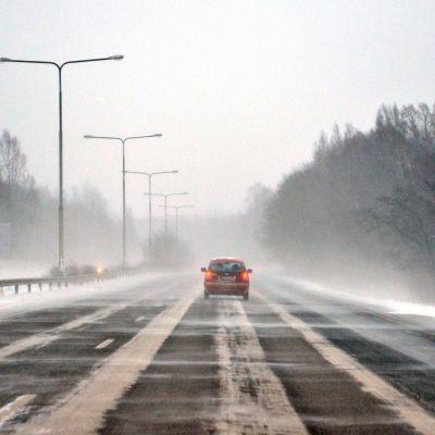 Auto moottoritiellä. Tuulee kovasti ja lumi pöllyää.