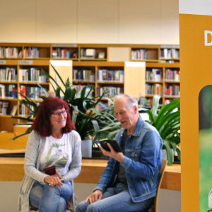 Nettiä ikä kaikki -tapahtuman kaksi kävijää Kuopion kirjastossa, etualalla SeniorSurf-toiminnan juliste.