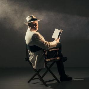 Mies (Jarmo Laitaneva) valkoisessa takissa ja valkoisessa hatussa istuu lukemassa kirjaa.