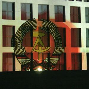 En husfasad. Till vänster vapnet för östtyska republiken DDR och till höger texten Humboldt Forum.