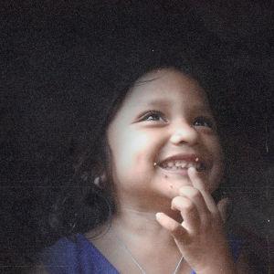 Hondurasilainen pikkutyttö hymyilee, kuvan tausta on tumma.