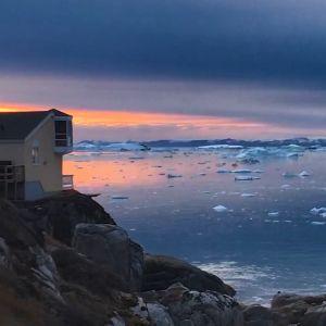 Ett hus på en klippa vid ett ishav.