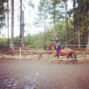 Rose-Marie Dahlström rider på en häst och skjuter med båge.