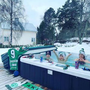 Tre glada barn i en badtunna tillsammans med Akilles-assecoarer.