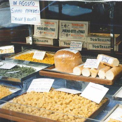 Bolognalaisen tuorepastakaupan näyteikkuna, jossa erilaisia irtopastoja sekä leipää.