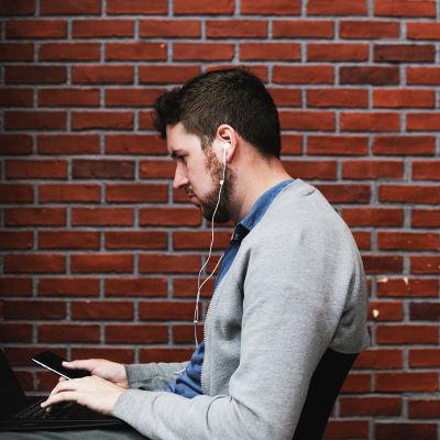 Kaksi miestä istuu tietokoneillaan selät vastakkain.