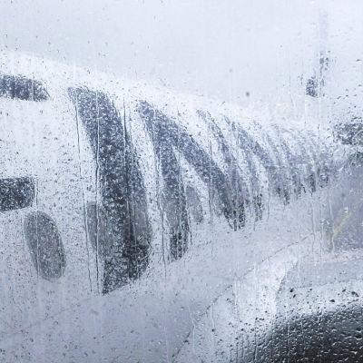 Regndroppar mot ett fönster. Man ser ett Finnair-flygplan från fönstret.