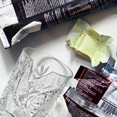 Olika typer av skräp mot en vit bakgrund. Till vänster finns ett söndrigt kristallglas, en havremjölkkartong, en nudelförpackning, ett munskydd, en plastkruka och omslaget till en buljongtärning.