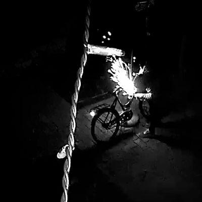 En tjuv söndrar ett cykellås med en batteridriven vinkelslip på natten.