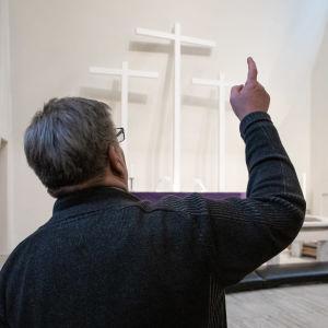 Kiinteistöpäällikkö Jari Nousiainen osoittaa Kolmen ristin kirkon alttaria johon aamu auringon säteet osuvat.