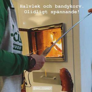 En person håller i en metallpinne med en korv på. Bakom i bild syns en öppen spis där en annan korv grillas.
