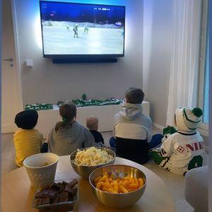 Flera barn sitter på golvet framför en tv. Bakom dem på ett bord finns skålar med chips och choklad.
