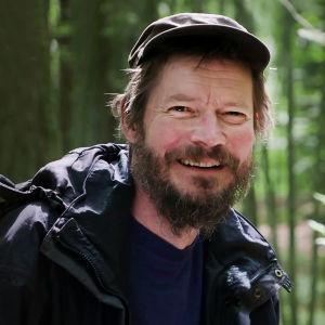 Kirjailija, näytelmäkirjailija ja ohjaaja Juha Hurme metsän keskellä