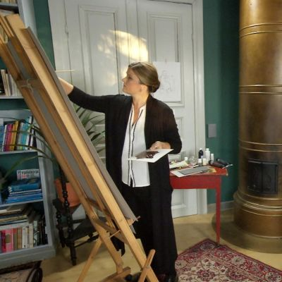 Camilla Forsén-Ström målar vid staffli.