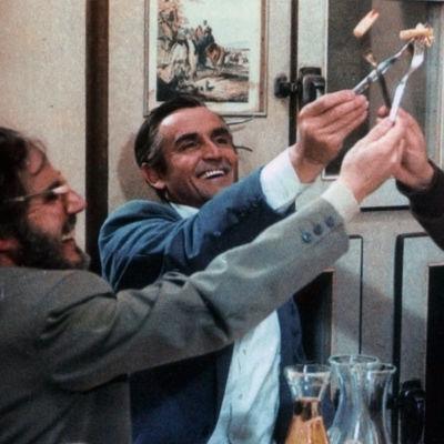 """Kolme miestä """"kippistää"""" haarukoilla ilmaan."""