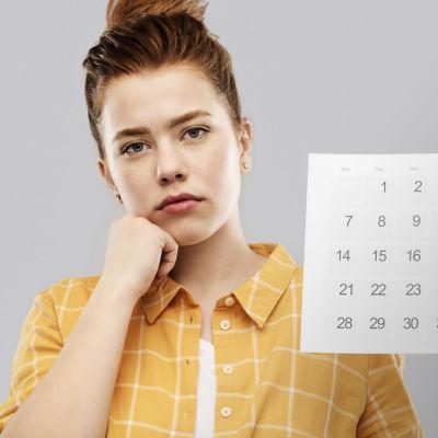 Vähän surullinen tyttö katsoo kameraan ja pitää kädessään paperista kalenteria.
