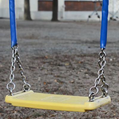 Tyhjä keltainen keinu leikkipuistossa.