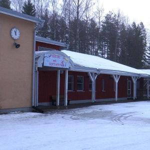 Skolbyggnad med röd fasad. På väggen hänger en klocka.