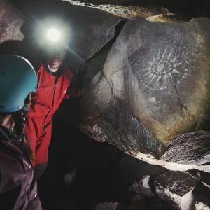 Kaksi henkilöä pimeässä luolassa valaisevat seinällä olevaa, aurinkoa muistuttavaa maalausta otsalampuillaan.