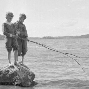 Pojat onkivat rantakivellä
