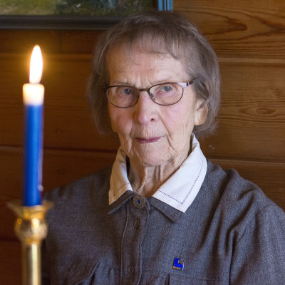 Ruusa Kemppainen katselee, sinivalkoinen kynttilä palaa pöydällä.