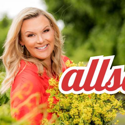 Programledaren Sanna Nielsen i röd skjorta gula blommor i famnen