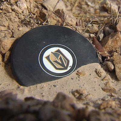 En puck med Golden Knights logo som ligger i sanden.