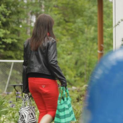 Nainen kauppakassien kanssa kävelee pihalla auton takana.