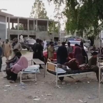 Människor väntade utanför sjukhuset i Harnai på torsdag morgon. Harnai ligger nära skalvets epicentrum i den pakistanska provinsen Baluchistan.