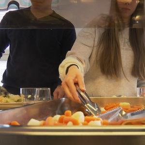 Två skolelever som tar åt sig skolmat