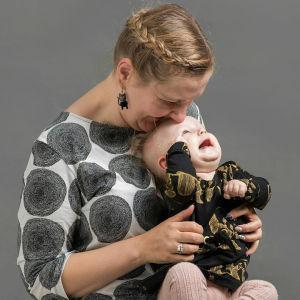 Suvi Tuoriniemi pitää lasta sylissään