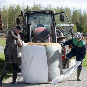 Två män jobbar med en höbal framför en traktor.
