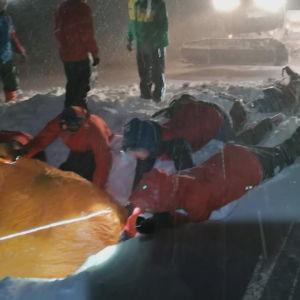 Avustustyöntekijät auttoivat lumen alle jäänyttä laskettelijaa Styriassa Itävallassa