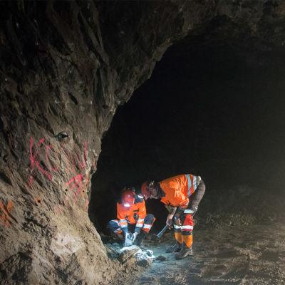 Kaivosmiehet tutkivat malmia tunnelissa.