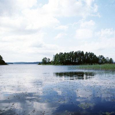 Pilvet heijastuvat tyynen järven pinnasta.