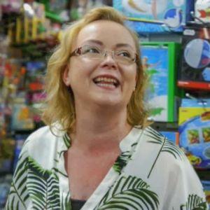 Myymälänhoitaja, silmälasit, vaalea pusero, vihreitä lehviä kuviona ,taustalla lelukauppaa