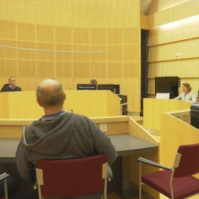 Bild inne från rättsalen. De åtalade i M/S Mässkär-rättegången sitter ner. Domare , nämdemän och åklagaren syns också.