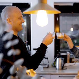 kaksi iloista miestä juo kahvia työpaikan viihtyisässä taukotilassa